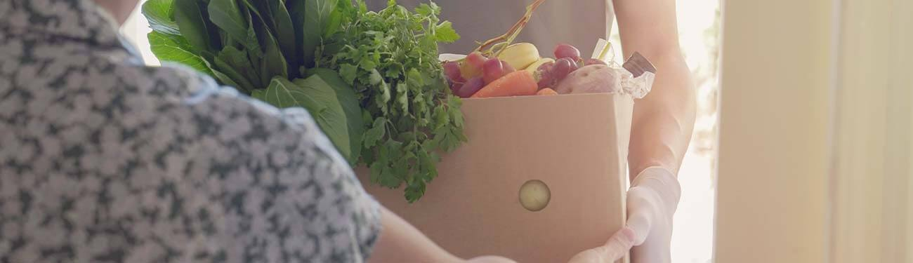 Person delivery box of produce to senior